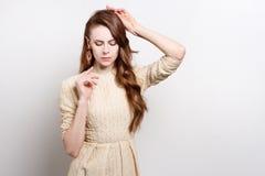 A jovem mulher atrativa no vestido dourado é estar, levantando suas mãos para sua cara Fotografia de Stock Royalty Free