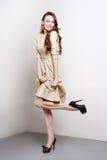A jovem mulher atrativa no vestido dourado sorri e está na pose da forma Fotografia de Stock Royalty Free