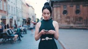 A jovem mulher atrativa no vestido preto ocasional e com rabo de cavalo bonito anda abaixo do centro da cidade histórico, e dos u filme