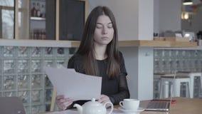 Jovem mulher atrativa no vestido preto que senta-se na tabela em documentos modernos da leitura do café O bule e o copo brancos e filme