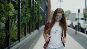 A jovem mulher atrativa nos óculos de sol e na roupa na moda que verifica o tempo em seu relógio anda perto do café da rua vídeos de arquivo