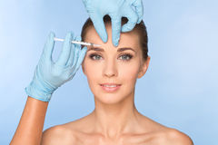 A jovem mulher atrativa obtém a injeção cosmética do botox foto de stock royalty free