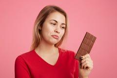A jovem mulher atrativa olha com expressão do descontentamento na barra de chocolate doce, mantém-se para fazer dieta, pode-se o  Fotos de Stock Royalty Free