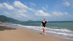 Jovem mulher atrativa que anda na praia A menina bonito tem o divertimento e a apreciação de feriados tropicais Menina bonita que video estoque
