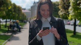 Jovem mulher atrativa que anda nas ruas ensolaradas da cidade e que conversa com amigos, menina alegre do moderno que usa o telef filme
