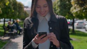 Jovem mulher atrativa que anda nas ruas ensolaradas da cidade e que conversa com amigos, menina alegre do moderno que usa o telef video estoque