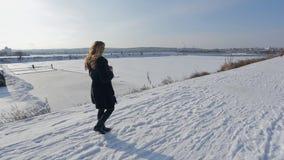 Jovem mulher atrativa que anda no inverno nevado fora vídeos de arquivo