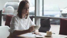 Jovem mulher atrativa que bebe o café fresco e que lê um compartimento do ` s das mulheres no café vídeos de arquivo