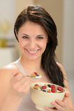 Jovem mulher atrativa que come a bacia de cereal Fotos de Stock Royalty Free
