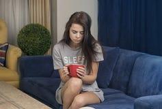 Jovem mulher atrativa que come o café no sofá no r vivo fotografia de stock royalty free