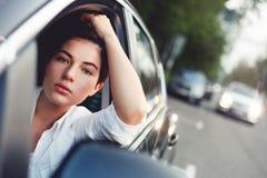 Jovem mulher atrativa que conduz o carro na estrada imagem de stock