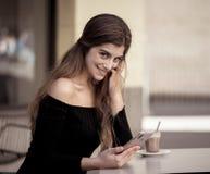 Jovem mulher atrativa que conversa e que data no telefone celular esperto na cafetaria fora da rua da cidade foto de stock