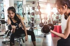 Jovem mulher atrativa que dá certo com pesos no gym Foto de Stock Royalty Free
