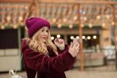 Jovem mulher atrativa que datilografa uma mensagem em um telefone celular, suporte Foto de Stock Royalty Free