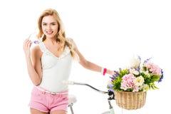 Jovem mulher atrativa que está pela bicicleta com as flores na cesta Imagens de Stock