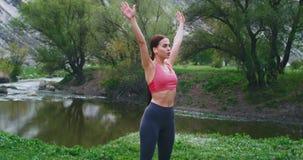Jovem mulher atrativa que estica o quando do corpo para tomar algum ar fresco na natureza com vista bonita, exercícios do tempo d filme