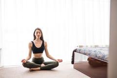 Jovem mulher atrativa que exercita e que senta-se na posição de lótus da ioga ao descansar em casa imagens de stock