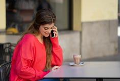 Jovem mulher atrativa que fala em seu telefone celular esperto em um terraço da cafetaria foto de stock