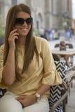 Jovem mulher atrativa que fala no telefone no café no dia ensolarado fotografia de stock