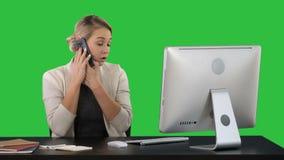 Jovem mulher atrativa que fala no telefone celular e que sorri ao sentar-se em seu lugar de trabalho no escritório e vista vídeos de arquivo