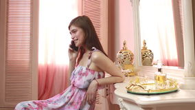 Jovem mulher atrativa que guarda e que usa o telefone celular em casa vídeos de arquivo