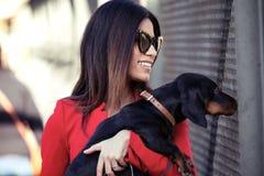 Jovem mulher atrativa que guarda seu cão pequeno ao andar à rua fotografia de stock