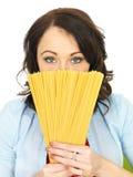 Jovem mulher atrativa que guarda um fã dos espaguetes secados sobre sua cara Fotografia de Stock