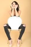 Jovem mulher atrativa que senta-se em uma cadeira em sapatas do salto alto fotografia de stock royalty free
