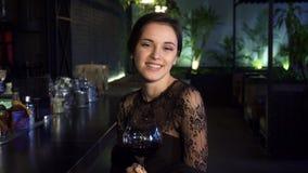 Jovem mulher atrativa que senta-se na barra que sorri à câmera com um vidro do vinho em sua mão filme