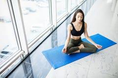 Jovem mulher atrativa que senta-se na posição dos lótus sobre o assoalho com os olhos fechados Imagem de Stock Royalty Free