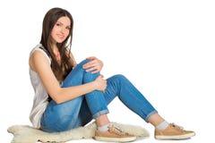 Jovem mulher atrativa que senta-se no assoalho isolado Foto de Stock