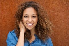 Jovem mulher atrativa que sorri com mão no cabelo Fotos de Stock