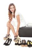 jovem mulher atrativa que tenta em diversos pares de sapatas novas Fotos de Stock