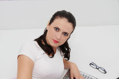 Jovem mulher atrativa que trabalha em seu portátil em casa Foto de Stock