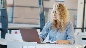 Jovem mulher atrativa que trabalha no local no kaye do verão O portátil dos usos toma notas em um caderno vídeos de arquivo