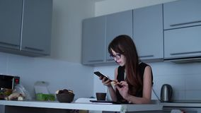 Jovem mulher atrativa que usa o smartphone e comendo na cozinha video estoque