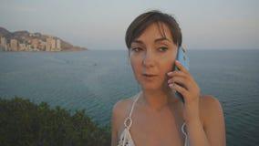 Jovem mulher atrativa que usa o smartphone Menina bonita que fala no telefone no balcão elevado do beira-mar do por do sol do ver vídeos de arquivo