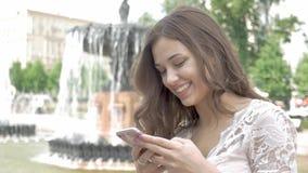 Jovem mulher atrativa que usa seu telefone celular móvel do tela táctil e sorrindo a si mesma filme