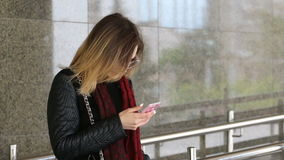 Jovem mulher atrativa que usa seu telefone celular móvel do tela táctil e sorrindo a si mesma vídeos de arquivo