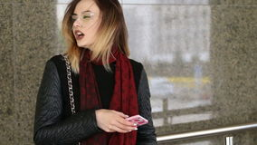 Jovem mulher atrativa que usa seu telefone celular móvel do tela táctil e sorrindo a si mesma video estoque