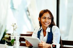 Jovem mulher atrativa que usa a tabuleta digital ao beber o café no café Imagem de Stock