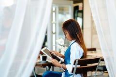 Jovem mulher atrativa que usa a tabuleta digital ao beber o café no café Imagens de Stock