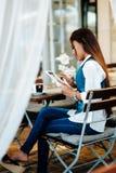 Jovem mulher atrativa que usa a tabuleta digital ao beber o café no café Foto de Stock