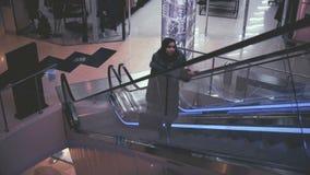 Jovem mulher atrativa que vai acima uma escada rolante filme