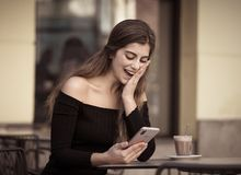 Jovem mulher atrativa que verifica o telefone celular feliz tendo lotes dos seguidores em seu blogue em linha fotos de stock