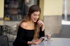 Jovem mulher atrativa que verifica o telefone celular feliz tendo lotes dos seguidores em seu blogue em linha fotografia de stock royalty free