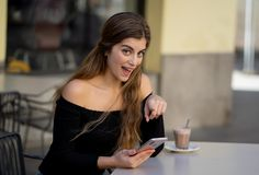 Jovem mulher atrativa que verifica o telefone celular feliz tendo lotes dos seguidores em seu blogue em linha foto de stock royalty free