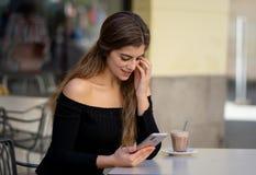 Jovem mulher atrativa que verifica o telefone celular feliz tendo lotes dos seguidores em seu blogue em linha imagens de stock royalty free