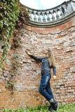 Jovem mulher atrativa séria na frente do tijolo Fotos de Stock Royalty Free