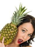 Jovem mulher atrativa saudável que guarda um abacaxi maduro fresco Fotografia de Stock Royalty Free